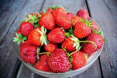在一块玻璃板的水多的草莓在木背景 免版税库存图片