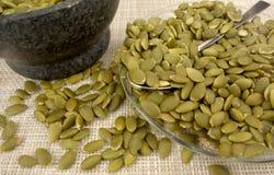在一块玻璃板的绿色南瓜籽 免版税库存照片