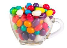 在一块玻璃的五颜六色的糖果在白色背景 免版税图库摄影