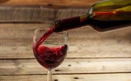 在一块玻璃的倾吐的红葡萄酒在木背景 库存图片