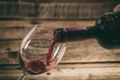 在一块玻璃的倾吐的红葡萄酒在木背景 免版税图库摄影