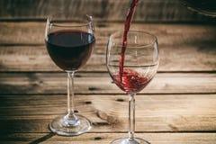 在一块玻璃的倾吐的红葡萄酒在木背景 库存照片