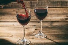 在一块玻璃的倾吐的红葡萄酒在木背景 图库摄影