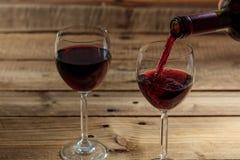 在一块玻璃的倾吐的红葡萄酒在木背景 免版税库存照片