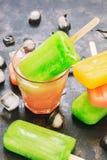 在一块玻璃的冰棍儿用汁液 五颜六色的冰棍儿,背后照明 绿色,黄色,桃红色 库存图片