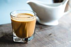 在一块玻璃的咖啡在一张木桌上 库存图片