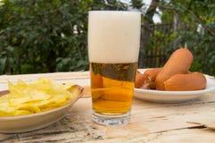 在一块玻璃的啤酒与泡沫,香肠,在板在庭院里,慕尼黑啤酒节题材的芯片 免版税库存图片