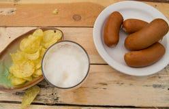 在一块玻璃的啤酒与泡沫,香肠,在板在庭院里,慕尼黑啤酒节题材的芯片 免版税图库摄影