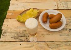 在一块玻璃的啤酒与泡沫,香肠,在板在庭院里,慕尼黑啤酒节题材的芯片 图库摄影