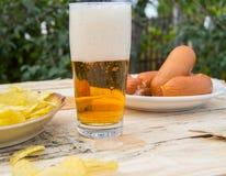 在一块玻璃的啤酒与泡沫,香肠,在板在庭院里,慕尼黑啤酒节题材的芯片 库存图片