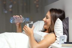 在一块玻璃的妇女投掷的水从一个瓶在床上 免版税图库摄影