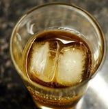 在一块玻璃的威士忌酒与冰和焦炭 库存图片
