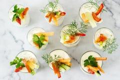 在一块玻璃的快餐与新鲜的奶油和各种各样的菜在轻的背景 免版税库存图片