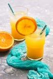 在一块玻璃的新鲜的橙汁与橙色切片 夏天刷新的饮料 免版税库存照片