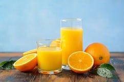 在一块玻璃的新鲜的橙汁过去在老木桌上 库存照片