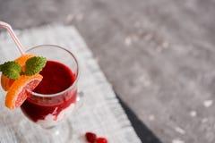 在一块玻璃的新鲜的草莓圆滑的人在灰色背景 免版税库存照片