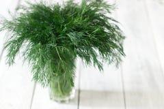 在一块玻璃的新鲜的莳萝在白色木背景 土气样式,选择聚焦 免版税图库摄影
