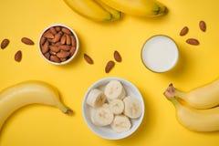 在一块玻璃的杏仁牛奶与杏仁坚果和香蕉在黄色 库存照片