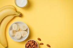 在一块玻璃的杏仁牛奶与杏仁坚果和香蕉在黄色 免版税图库摄影