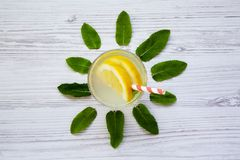 在一块玻璃的柠檬水饮料与在白色木背景,顶视图的秸杆 创造性的夏天 库存图片