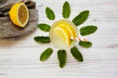 在一块玻璃的柠檬水饮料与白色木表面,顶视图上的秸杆 免版税库存图片
