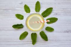 在一块玻璃的柠檬水饮料在白色木背景,顶视图 创造性的夏天 图库摄影