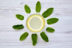 在一块玻璃的柠檬水饮料在白色木背景,顶视图 创造性的夏天 库存照片