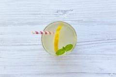 在一块玻璃的柠檬水饮料用新鲜的柠檬和薄菏在白色木背景,顶视图 免版税库存图片