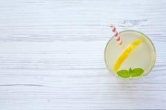 在一块玻璃的柠檬水饮料用新鲜的柠檬和薄菏在白色木背景,顶视图 免版税库存照片
