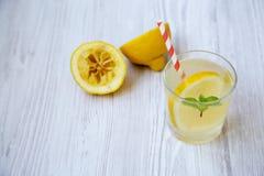 在一块玻璃的柠檬水饮料用新鲜的柠檬和薄菏在白色木背景, 免版税库存图片