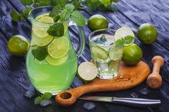 在一块玻璃的柠檬水mojito在黑木背景 免版税库存图片