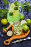 在一块玻璃的柠檬水mojito在黑木背景 库存照片