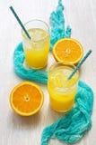 在一块玻璃的橙汁与在圆点的秸杆和与在一张白色木桌上的一块蓝色餐巾 夏天的概念 免版税图库摄影
