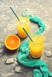 在一块玻璃的橙汁与在灰色背景的一块蓝色餐巾 有选择性的选择 夏天的概念 被定调子的照片 免版税库存图片