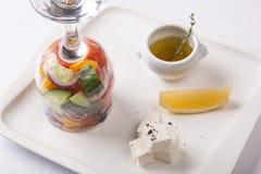 在一块玻璃的沙拉用柠檬和乳酪 库存照片