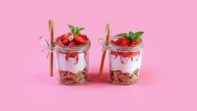 在一块玻璃的点心与格兰诺拉麦片、酸奶和草莓 在桃红色背景隔绝的有用的早餐 地道生活方式图象 免版税库存图片