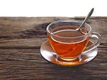 在一块玻璃的热的茶在一张木桌上 库存照片