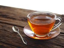 在一块玻璃的热的茶在一张木桌上 图库摄影