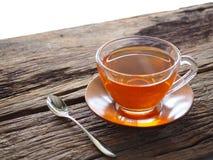 在一块玻璃的热的茶在一张木桌上 库存图片