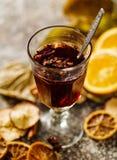 在一块玻璃的热的酒在一张桌上用干果子 库存照片