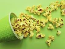 在一块玻璃的玉米花在一道绿色背景背景开胃菜 免版税库存图片