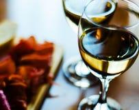 在一块玻璃的白葡萄酒用在一张木桌,集合o上的开胃菜 图库摄影