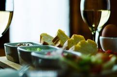 在一块玻璃的白葡萄酒用在一张木桌,集合o上的开胃菜 库存照片