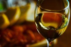 在一块玻璃的白葡萄酒用在一张木桌,集合o上的开胃菜 库存图片