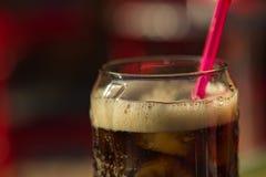 在一块玻璃的碳酸化合的饮料与管关闭 图库摄影