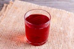 在一块玻璃的红色汁液在桌上 库存图片
