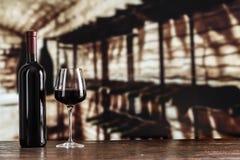 在一块玻璃的红葡萄酒在地窖的背景 库存图片
