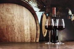 在一块玻璃的红葡萄酒在桶背景在地窖里 库存照片