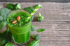 在一块玻璃的绿色健康圆滑的人用硬花甘蓝、菠菜、杏仁和chia种子 图库摄影
