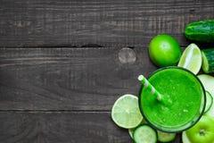 在一块玻璃的绿色健康圆滑的人用菠菜、苹果、黄瓜和石灰与秸杆在土气木桌 库存照片